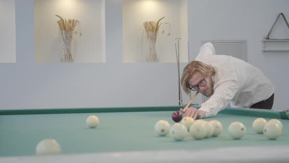 Thumbnail for Blond Bearded Man Playing Pool, Billiards in Light Room. Confident Player Hits the Ball with a Cue