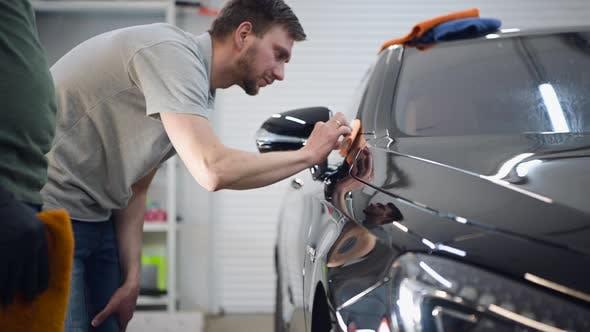 Professioneller Auto-Keramik-Arbeiter wendet eine Schicht Keramik-Schutzabdeckung auf ein Auto an