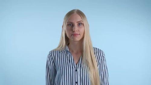 Blonde junge Frau Missverständnis etwas auf blauem Hintergrund.