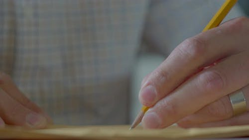 Male Hand Writing With a Pencil on a Yellow Envelope Close Up