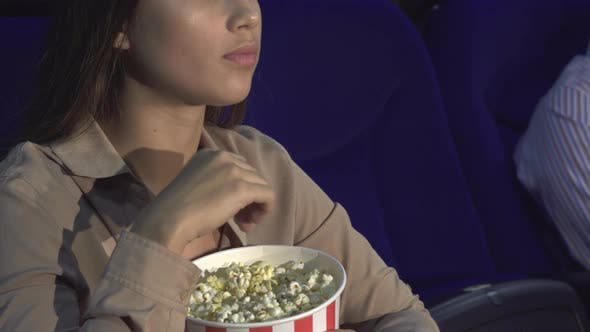 Thumbnail for A Close-up of How a Girl Eats Popcorn and Shows a Sign of Silence