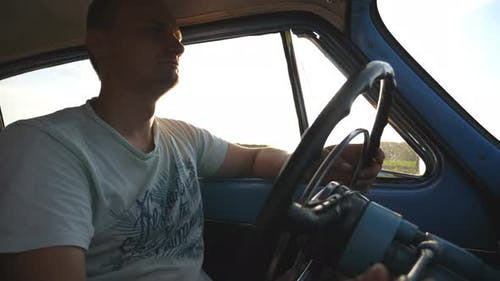 Caucasian Man Holding Hands on Steering Wheel and Driving a Retro Car at Sunset