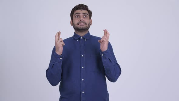 Cover Image for Young Bearded Indian Businessman Wishing with Fingers Crossed