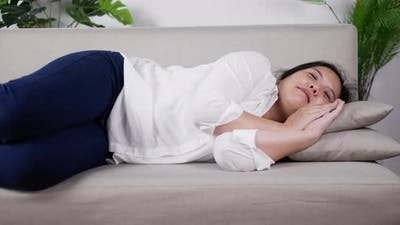 Young woman lying on sofa watching on TV in living room