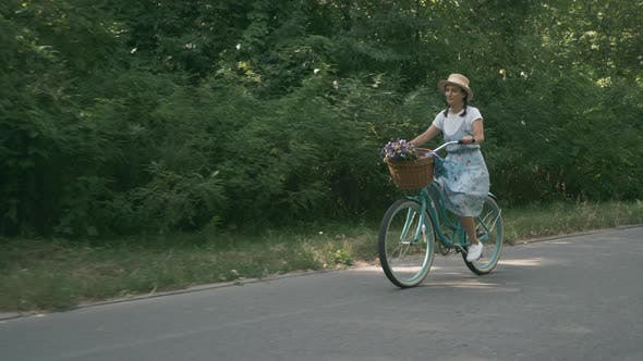 Thumbnail for Female cyclist is pedaling on old bike. Brunette girl in hat rides bicycle