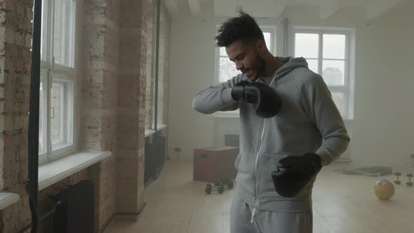 Afro Sportsman Putting On Boxing Gloves