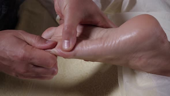 Specialist Does Foot Massage in Beauty Salon. Close-up View