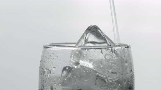Thumbnail for Pouring Up Shot of Vodka From a Bottle Into Glass. White Background