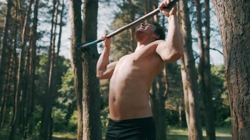 Strong Man Performing Exercises on the Uneven Bars, Sport and Healthy Lifestyle. Close Up of Strong