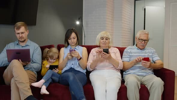 Addicted To Gadgets Family Using Mobile Phone, Tablet, Laptop Ignoring Each Other at Home. Obsession
