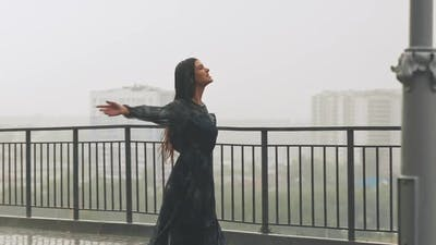 Pretty Woman Turns Dancing Under Heavy Rain on Viewpoint