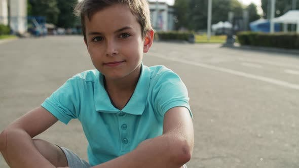 Thumbnail for Cute Boy Sitting in Amusement Park. Close Up Relaxed Teen Boy Outside