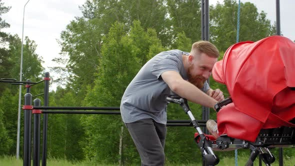 Thumbnail for Caucasian Dad Exercising with Friend and Baby Girl at Outdoor Gym