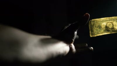 Concept of Unemployment, Poverty. Man Hand Reaches for Dollar Bill on Black Background