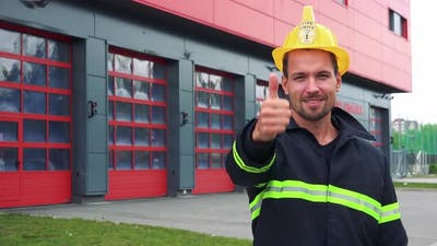 A Young Firefighter Shows a Thumb Up To the Camera with a Smile - a Fire Station in the Background