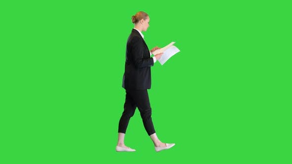 Young Business Woman Looking Through Documents While Walking on a Green Screen Chroma Key
