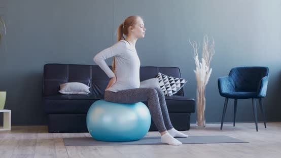 Pregnant Woman Exercising on Fitball at Home
