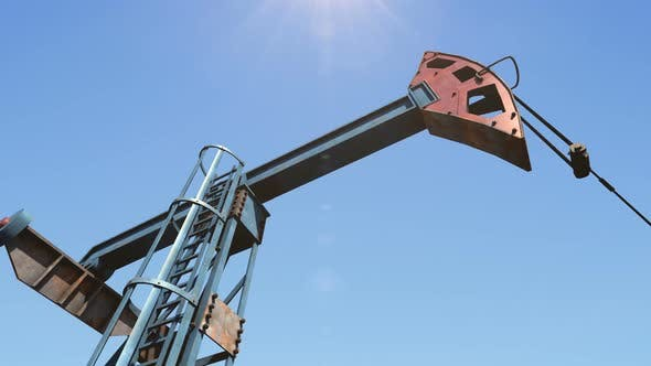 Low Angle Shot of Oil Pump Jack Pumping Crude Oil under Clear Blue Sunny Sky
