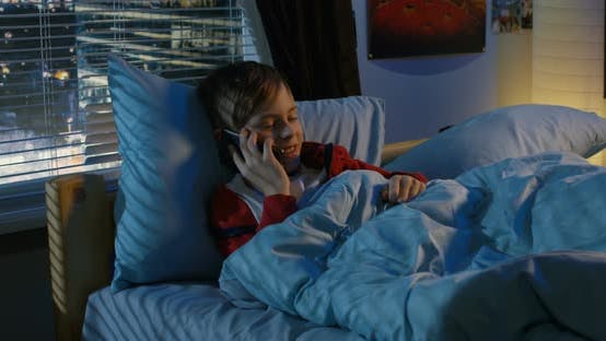 Thumbnail for Boy Making a Call While Lying in Bed