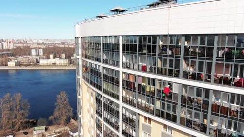 Industrial Climber Cleans Window of Hotel Near River