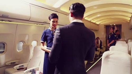Cabin Crew Greeting Passenger in Airplane