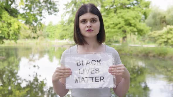 A Young Caucasian Woman Shows a Black Lives Matter Sign to the Camera in a Park