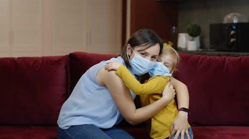 Little Daughter Puts on Sick Mother Protective Medical Mask at Home. Coronavirus Quarantine Lockdown