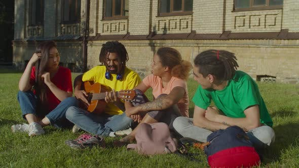 Thumbnail for Multiracial Students with Guitar Resting at Campus