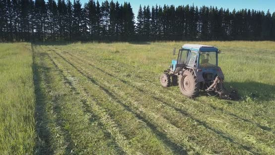 Thumbnail for Farmer Operates Tractor Mowing Grass for Hay in Countryside