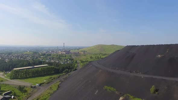 Thumbnail for Aerial view of Huge slag dump next to residential buildings and vegetable gardens