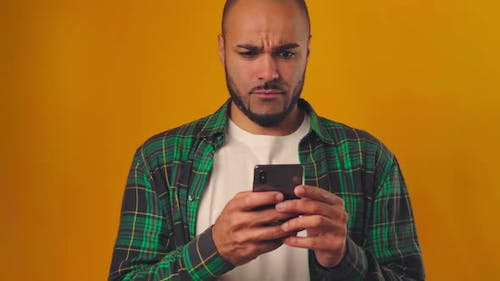 Confused and Surprised African American Man Typing on His Mobile Phone Against Yellow Background
