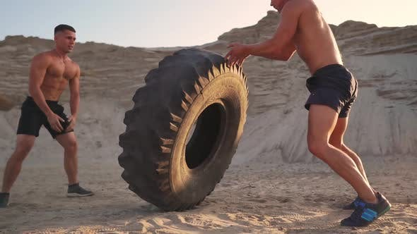 Thumbnail for Two Muscular Open-chested Athletes Train in Active Mode on the Beach Doing push-UPS