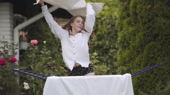 Thumbnail for Funny Cute Young Woman Have Fun Dancing at the Backyard While Doing House Work with the Linen