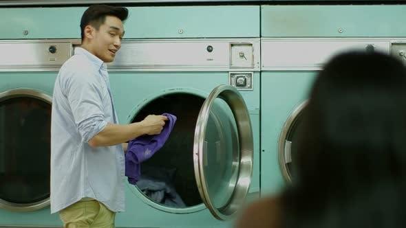 Thumbnail for Ein junger Mann und eine junge Frau treffen sich in einem Waschsalon während der Wäsche