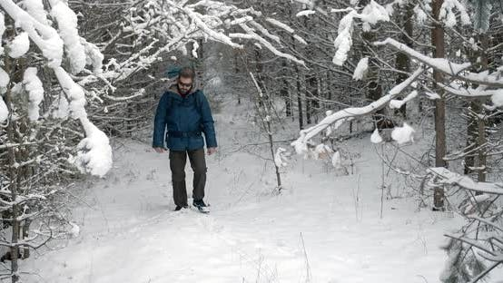 Thumbnail for Male Tourist with Backpack Walking on Snowy Forest