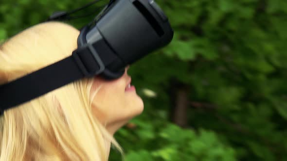 Thumbnail for Young Attractive Blond Woman Walks and Uses Virtual Reality Glasses
