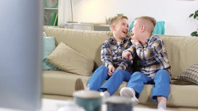 Caucasian Identical Twins Watching TV and Rolling with Laughter