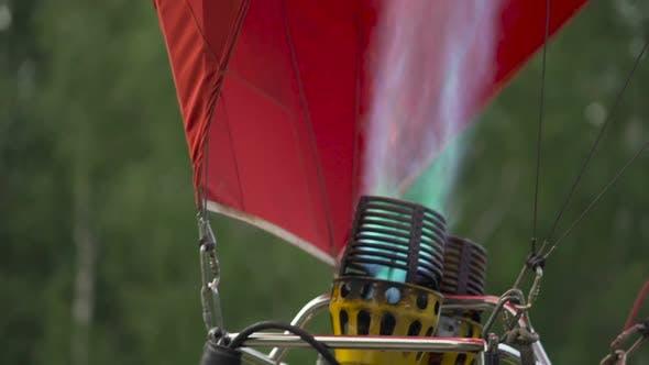 Thumbnail for Close-up of hot air balloon burner inflating envelope, preparing for flight