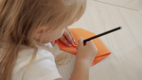 A Girl in Kindergarten or at Home Paints a Figure Out of Paper