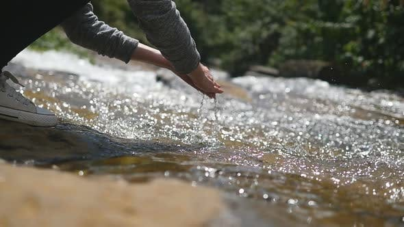 Young Female Hiker Washes Her Hands in Clear Water of Mountain River. Unrecognizable Woman Refreshes
