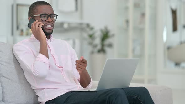 Thumbnail for African Man with Laptop Talking on Smartphone at Home