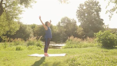 Woman exercising in park in the morning. Female doing meditation exercises at sunrise