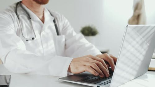 Midsection of Male Physician in Lab Coat Working on Laptop