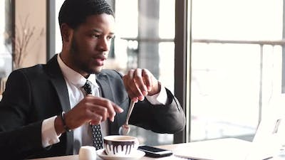 Businessman Working Remotely with Laptop at Cafe