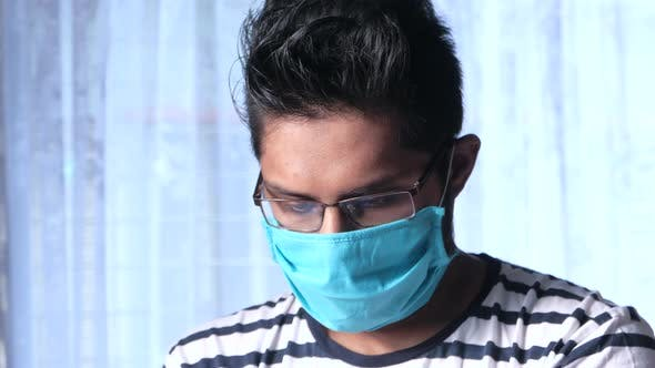 A Young Asian Man with Protective Mask Feeling Sick