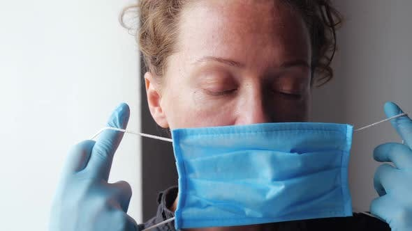 Thumbnail for Woman in Rubber Gloves Puts on Medical Protective Mask. Looking at the Camera Close-up. Concept of