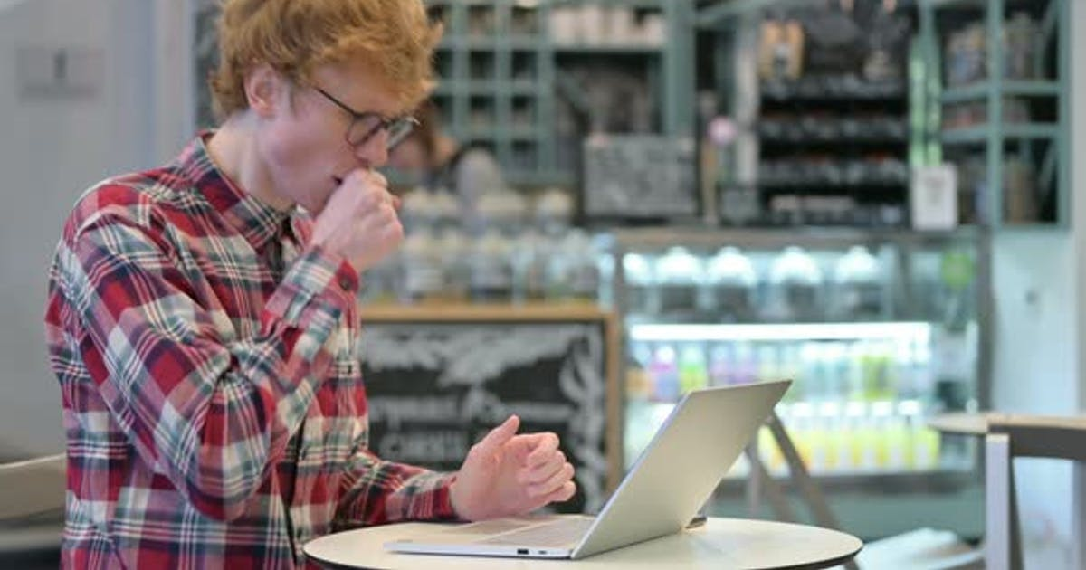 Young Redhead Man with Laptop in Cafe Coughing