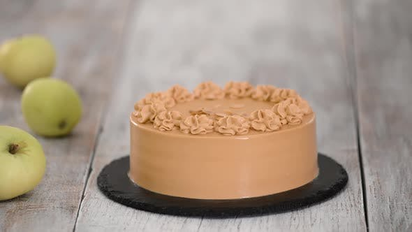 Thumbnail for Pastry Chef Sprinkles of Almond Flakes on a Caramel Cake.