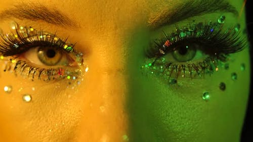 Womens Eyes with Sparkles and Rhinestones, Illuminated with Yellow and Green Neon Light, Look