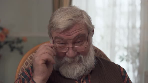 Thumbnail for Portrait of Adult Darling Grandfather with a Big Beard and a Kind Look Who Corrective Glasses on the